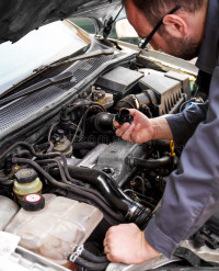 mechanic-checks-oil-car-being-repaired-53610254